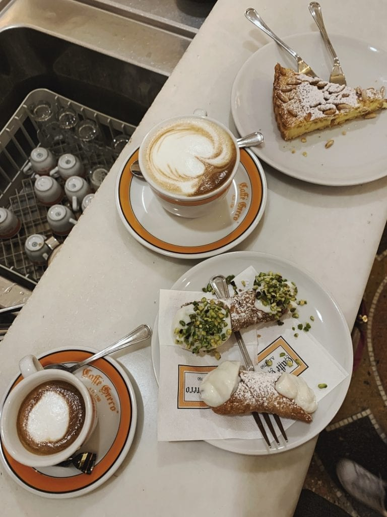 classic italian coffee with a few sicilian cannolo and a piece of cheesecake from cafe greco