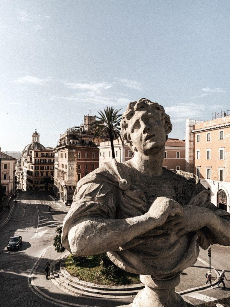 a romanesque sculpture in villa aldobrandini with modern rome city as background