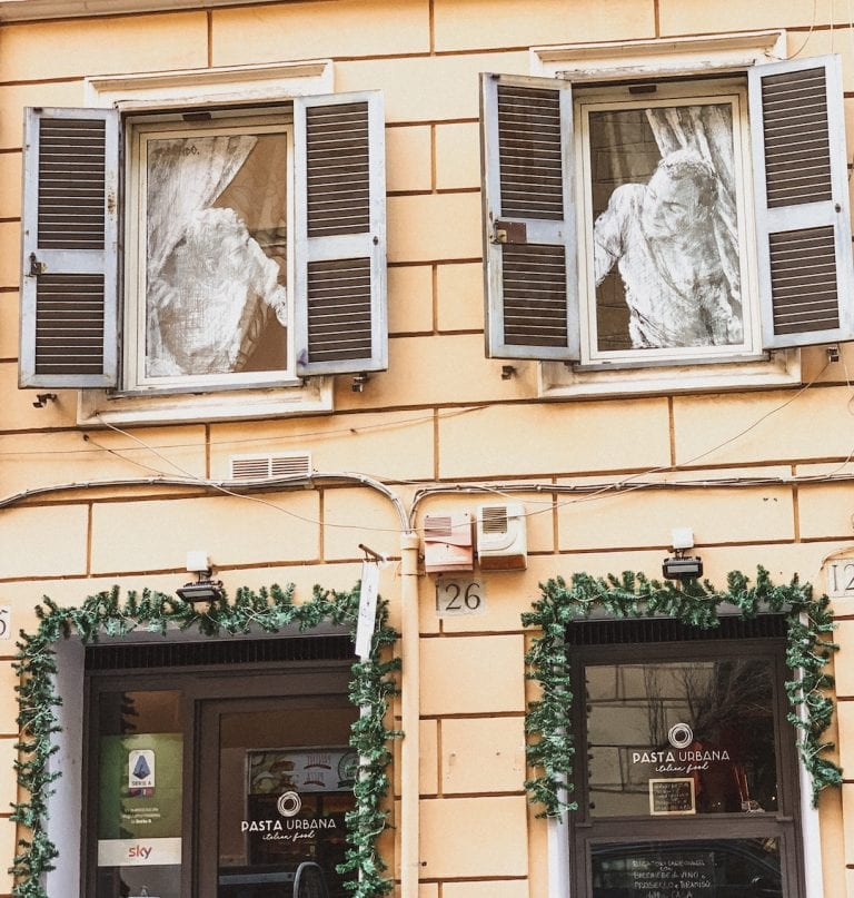 the funny street art about neighbors on the buildings in cavour