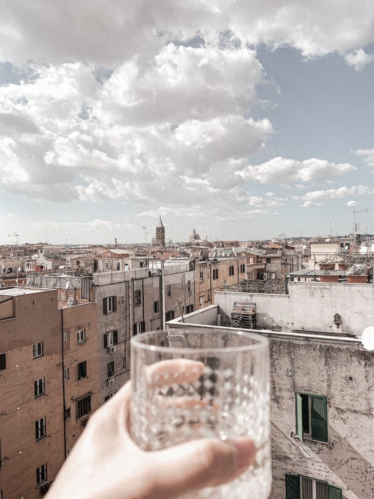 drinking wine on rooftop to enjoy the sunny day in rome while doing quarantine and social distancing in coronavirus situation