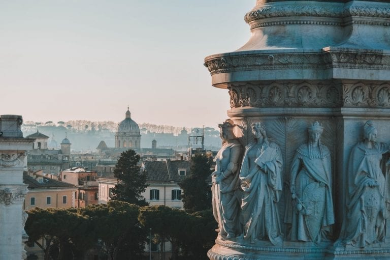 the details on the marble column in Rome with Rome city and Vatican as a background