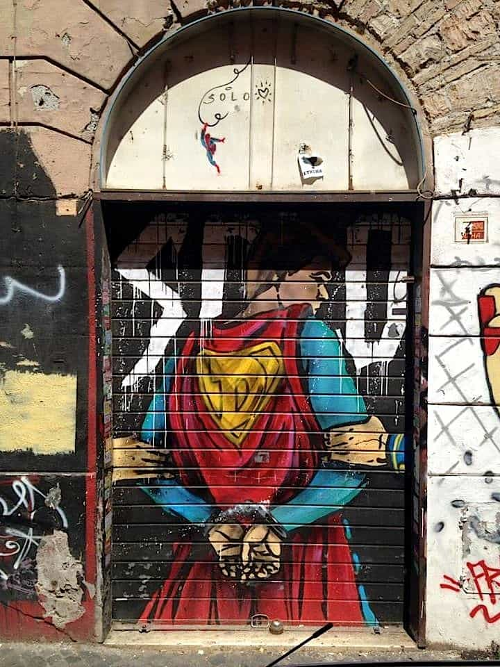 modern superman graffiti on a shop roller shutter in san lorenzo one of the famous art district and Rome street art district