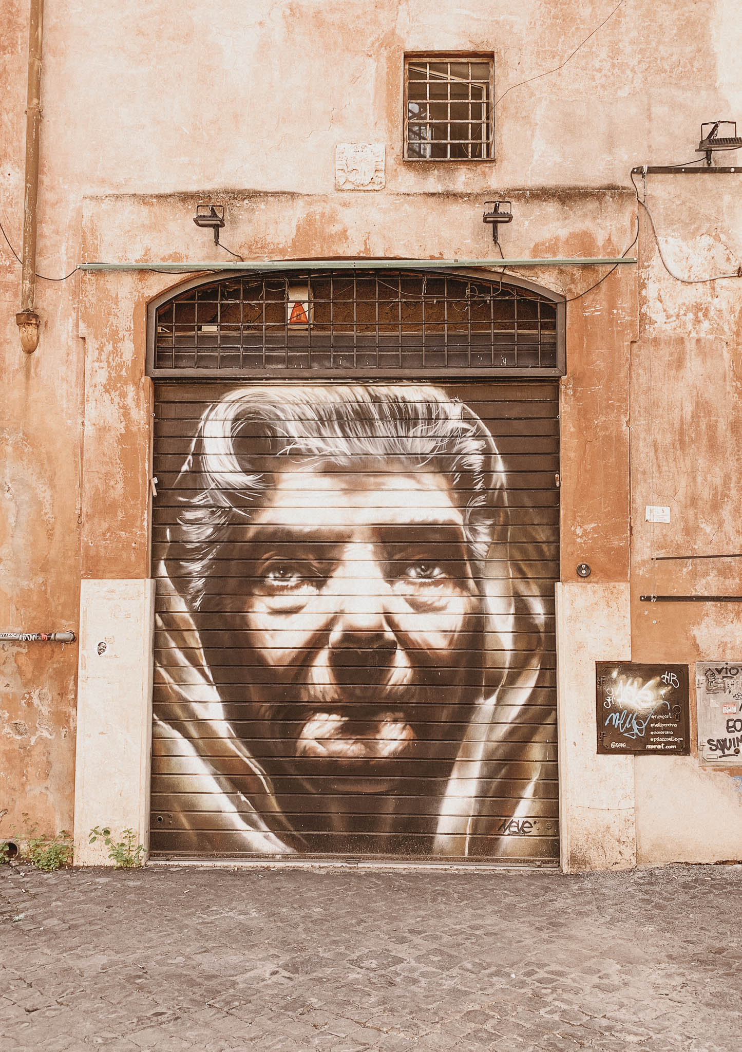 powerful and determined italian grandma graffiti on a shop roller shutter in trastever Rome