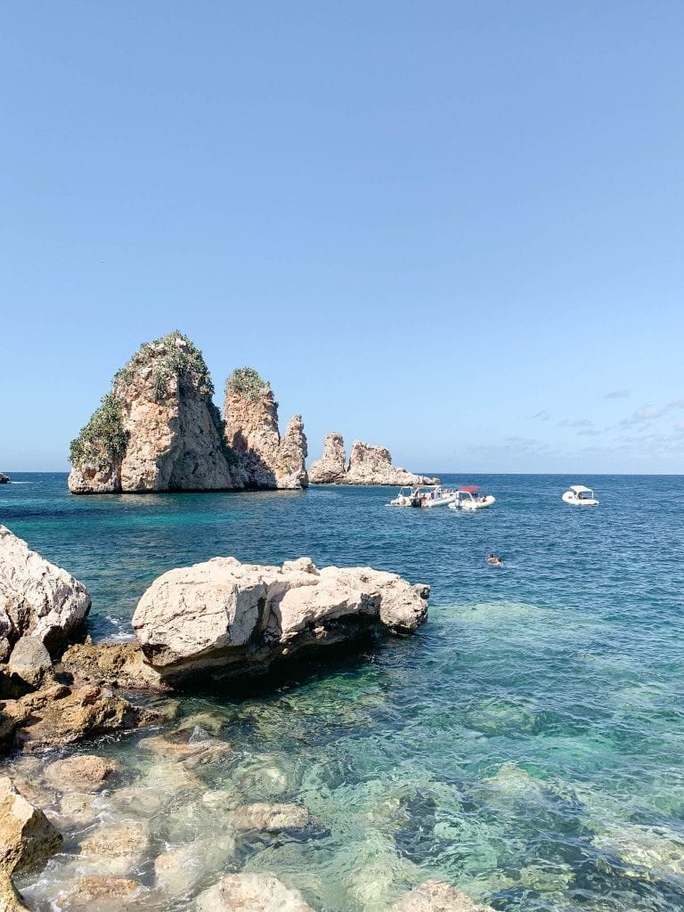the stunning view with crystal clear water in different blues of tonnara di scopello
