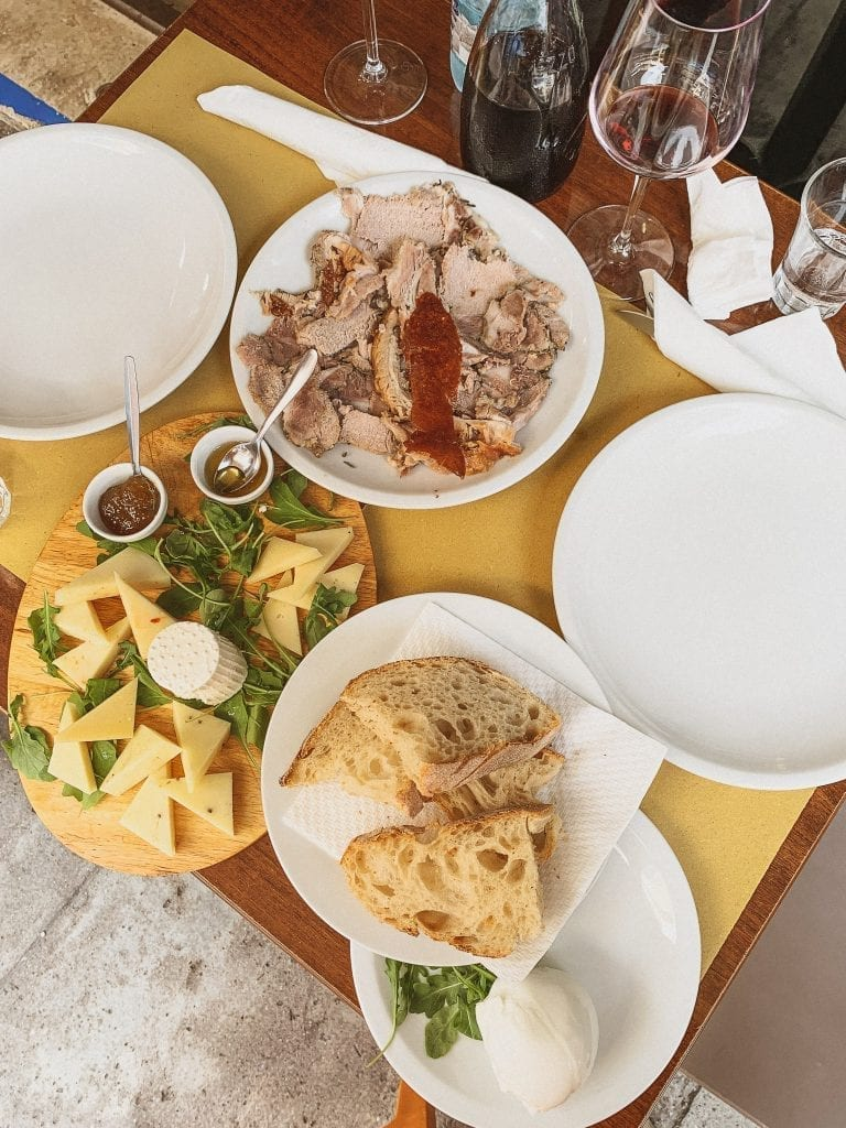 Enjoy the Fraschetta type of Aperitivo in Rome with porchetta, cheese and meat platter, and chilled red wine in the out-of-the-city neighborhood