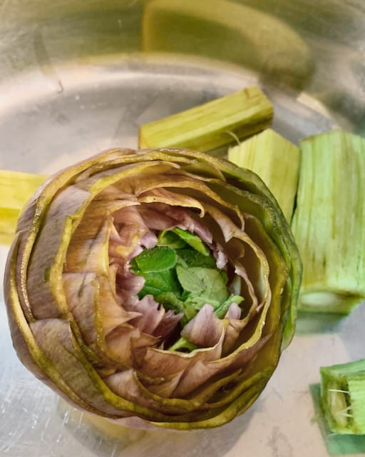 Mentuccia and garlic is a pair when cooking with artichokes. They create a good balance for the rich and fresh taste. Normally you chopped a little and stuff them in the centre of the cleaned artichokes.